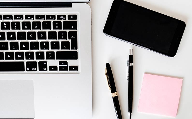 laptop mobile, pens and post it notes, cv mistakes